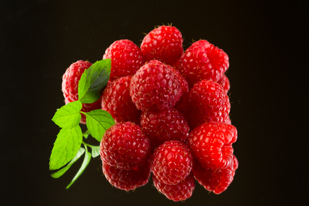 Stack of fresh, delicious, organic, ripe raspberries, green leaves on black  Stock Photo