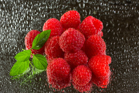 Stack of fresh, delicious, organic, ripe raspberries, green leaves under rain on black