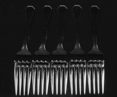 Set of stainless steel fork reflection on black background