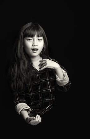 Portrait of cute little girl painting on black background Stock Photo