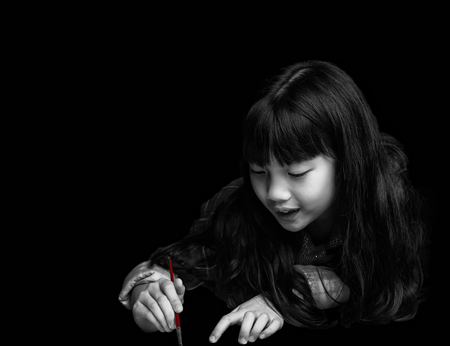 Cute little girl is painting on black background