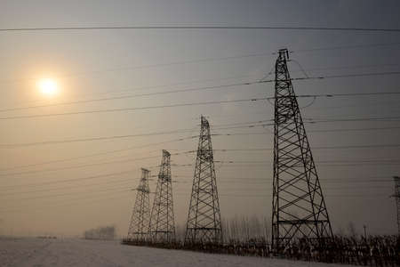 Stand high voltage towers in the snowy fields photo