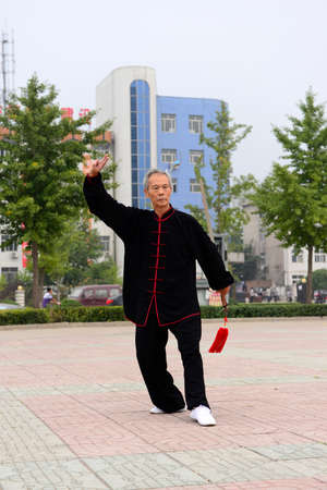 poise: Luannan - September 20: an old man fencing in cultural activities square, the performance on September 20, 2014, the south of the luanhe river, hebei, China. Editorial