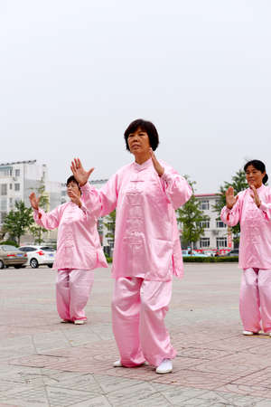poise: Luannan - September 20: women perform taijiquan in cultural activities square, on September 20, 2014, the south of the luanhe river, hebei, China.