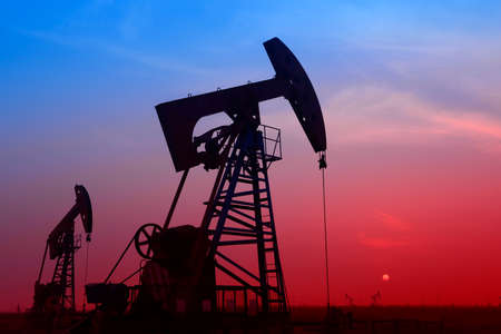 oil well: Operaci�n aislada de la unidad de bombeo bajo el sol poniente