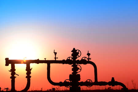 Oil pipeline features, under the sunset of oilfield Stock Photo