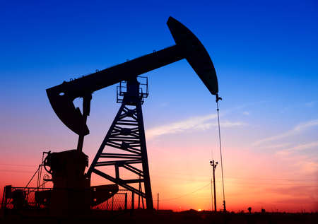 Is operation of pumping unit under the sunset of oilfield, close-up Stock Photo