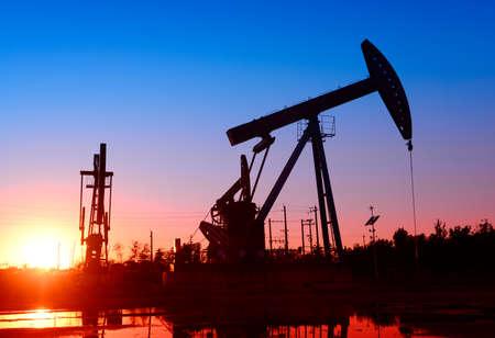 yacimiento petrolero: la unidad de bombeo en el yacimiento, la puesta del sol, primer plano