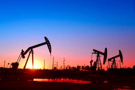 yacimiento petrolero: Es el funcionamiento de la unidad de bombeo en la puesta del sol del campo petrolífero, primer plano