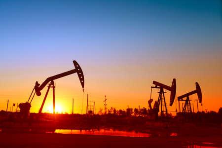 yacimiento petrolero: unidad de bombeo en la puesta del sol del campo petrolífero, primer plano
