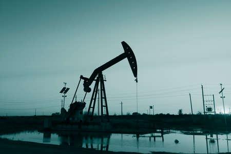 yacimiento petrolero: unidad de bombeo en la puesta del sol del campo petrol�fero, primer plano