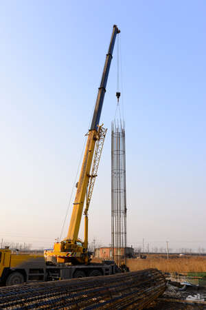 erecting: Crane lifting steel bars Stock Photo