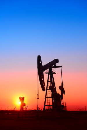 Working oil derrick in field under the setting sun