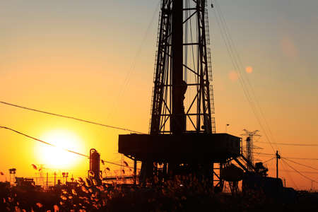 oil derrick: The oil derrick, under the setting sun