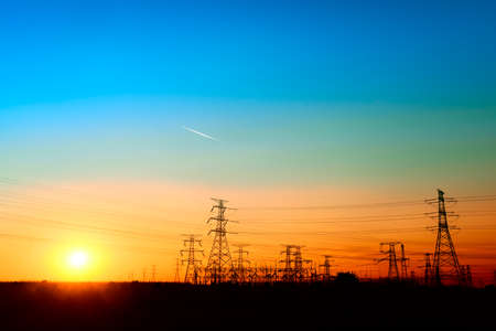 High voltage towers under the setting sun Imagens - 91424396