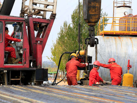 Oil workers are working at the oil fields  Editorial