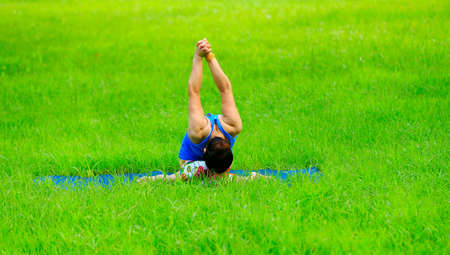 A woman is practicing yoga on the grass Stock Photo
