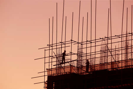 Construction workers work in silhouette at sunset