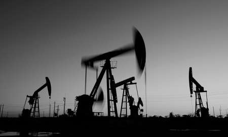 Oil pumps in action, silhouetted against the setting sun