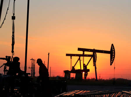 The oil workers are working in the sunset silhouettes