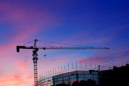 Cranes at construction sites, silhouetted at sunrise