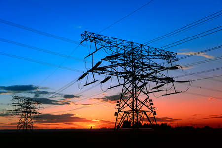 High voltage towers, silhouetted in the setting sun
