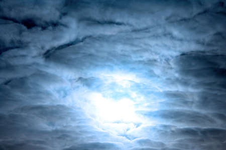 The fantastic sky with clouds and the sun... or the moon Stock Photo