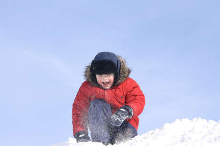 The boy, in the winter throwing snow upwards