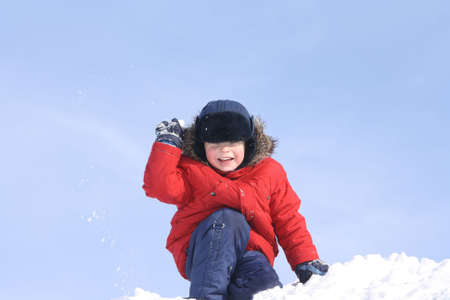 The boy, in the winter a throwing snowball