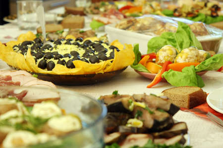 The table covered with different dishes - fish, meat, various salads, greens