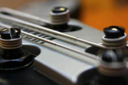 Splittings on a bass guitar with the tense silvery strings