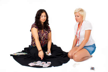Two women sit and tell fortune on a white background