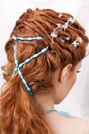 Hairdress of the red-haired girl with blue ornaments Stock Photo