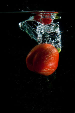 Sweet pepper plunges into water with vials