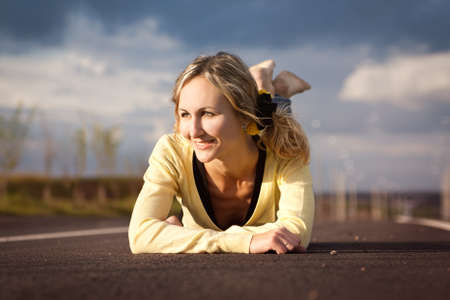 The girl lies on road, looks aside and smiles photo