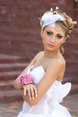 Bride with flowers on her arm near the stairs photo