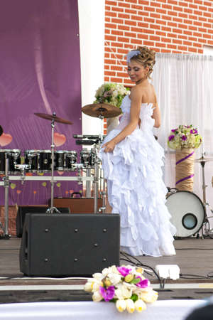 Bride poses on stage with musical instruments