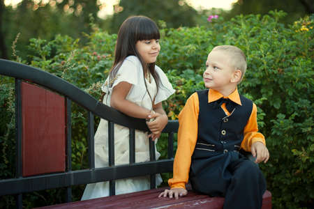 little boy and girl sitting on a bench,  boy and girl looking on