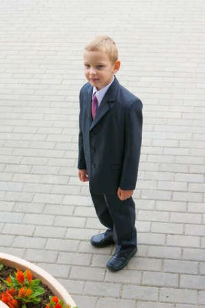 Cute young boy in suit and tie looking up photo