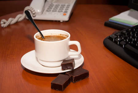 Cup photo on an office desk with a phone in the background Stock Photo