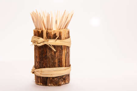 Wooden toothpicks in a stand on a white background