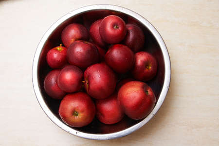 Red juicy apples in a bowl on the table top view Stock Photo