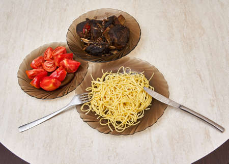 Plates on the table with fried meat, pasta and tomatoes, served for lunch