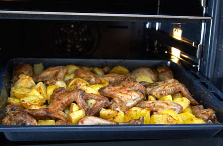 Fried potatoes with wings and drumstick chicken in the oven Stock Photo