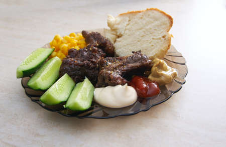 Meat roasted prime rib, fresh cucumbers, corn and homemade bread on a plate on the table photo