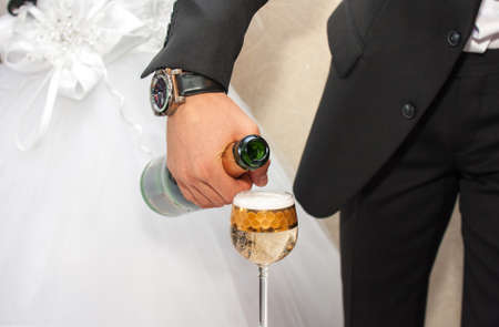 Pouring champagne into a glass on a wedding celebration photo