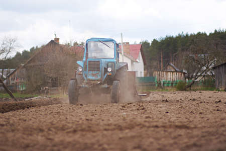 Farmer in tractor preparing land for sowing photo