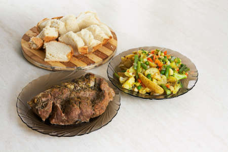 Two plates with baked meat and assorted fruits and homemade bread