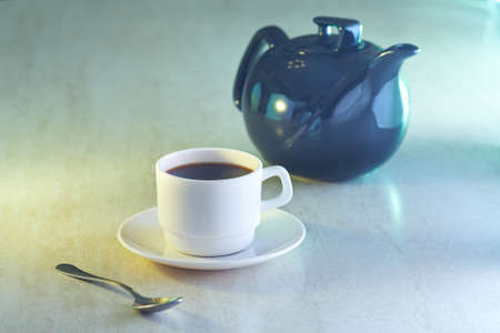 Coffee cup and kettle in light on table photo