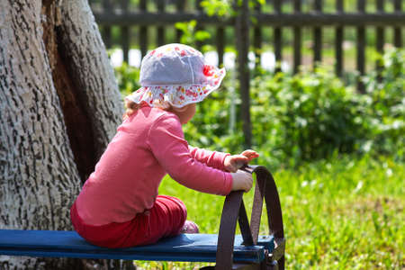 little girl sitting on the bench in park Stock Photo